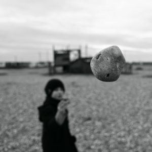 A stone seems to float in mid-air in front of a child, frozen in the frame